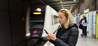 Woman with a cell phone waiting for metro. Young casual woman using mobile phone in her hand waiting on the platform of a metro station for metro to arrive Royalty Free Stock Photo