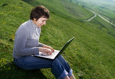 Young casual woman working on laptop Stock Images