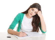 Young casual woman writing in workbook. Royalty Free Stock Image