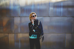 Young casually-dressed woman having mobile phone conversation while waiting for someone outside. Half length portrait of hipster girl using cellphone for call to Stock Image