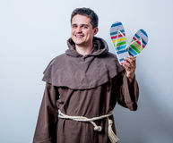 Young catholic monk with vacation flip flops Royalty Free Stock Photos
