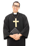 Young Catholic priest holding the holy bible Royalty Free Stock Image