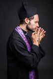 Young catholic priest praying. Studio portrait on black background Royalty Free Stock Images