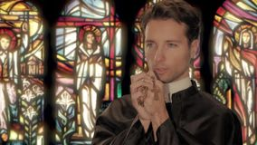 Young catholic priest saying a prayer stock video footage