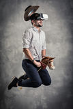 Young caucasian adult man enjoy experiencing immersive Virtual Reality cowboy game simulation.VR portrait concept with. Western horse and hat royalty free stock image