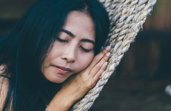 Young caucasian asian girl swinging in a hammock in a pleasant laziness of a weekend evening. She is smiling through her beard., holiday at riverside in royalty free stock images