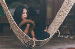 Young caucasian asian girl swinging in a hammock in a pleasant laziness of a weekend evening. She is smiling through her beard., holiday at riverside in royalty free stock photography
