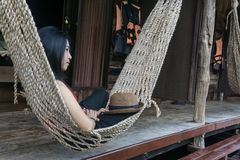 Young caucasian asian girl swinging in a hammock in a pleasant laziness of a weekend evening. She is smiling through her beard., holiday at riverside in royalty free stock photos