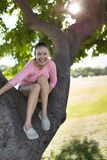 Young Caucasian/Asian woman smiling and happy, having fun sitting on a tree during a summer afternoon at the park. Girl is having a great time hanging out high Stock Photography