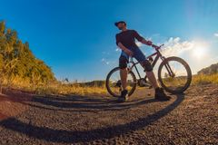 Young caucasian athletic  man in a  knee pads  relies on a  spor. Ts bike and staring into the distance on an colorful autumn background with a bright blue sky Royalty Free Stock Photo
