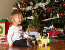 Young caucasian baby girl opening presents at xmas Stock Photo