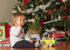 Young caucasian baby girl opening presents at xmas Royalty Free Stock Images