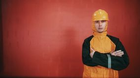 Guy in builder suit and orange hard hat cross armed in red room, rapping stock footage