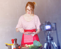 Woman cooking for Video-sharing website. Young caucasian blogger woman cooking at camera for Video-sharing website. Home location at kitchen Royalty Free Stock Photography