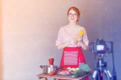 Woman cooking for Video-sharing website. Young caucasian blogger woman cooking at camera for Video-sharing website. Home location at kitchen Stock Photo