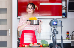 Woman cooking for Video-sharing website. Young caucasian blogger woman cooking at camera for Video-sharing website. Home location at kitchen Stock Photography
