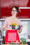 Woman cooking for Video-sharing website. Young caucasian blogger woman cooking at camera for Video-sharing website. Home location at kitchen Royalty Free Stock Image