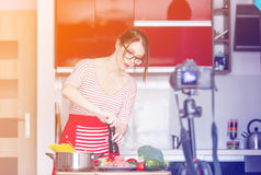 Woman cooking for Video-sharing website. Young caucasian blogger woman cooking at camera for Video-sharing website. Home location at kitchen Royalty Free Stock Images