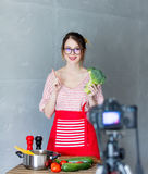 Young caucasian blogger woman cooking Vegan food. At camera for Video-sharing website. Home location at kitchen royalty free stock photography