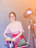 Young caucasian blogger woman cooking Vegan food. At camera for Video-sharing website. Home location at kitchen royalty free stock images