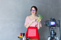 Young caucasian blogger woman cooking Vegan food. At camera for Video-sharing website. Home location at kitchen stock images