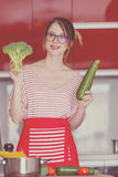 Young caucasian blogger woman cooking Vegan food. At camera for Video-sharing website. Home location at kitchen stock image