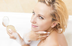 Young Caucasian Blond Female Doing Makeup During Bathing Process.Positive Facial Expression. Skin Treatment Procedure. Stock Photo