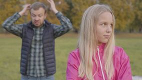Young caucasian blonde girl with light brown eyes standing on the autumn meadow and listening to the adult man shouting. At her on the background. Daughter stock video