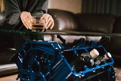 Young caucasian blonde girl sitting on sofa with glass of whiskey at luxury interior with custom v8 car engine table. Fashion stock images