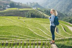 Young Caucasian blonde woman in denim shirt overlooking Sapa rice terraces at sunset in Lao Cai province, Vietnam