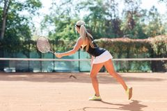 Young caucasian blonde woman is playing tennis outdoor. View from back. Tennis player in action. Horizontal image stock photo