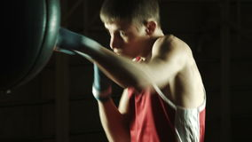 Young caucasian Boxer training with a punching bag in gym stock video footage