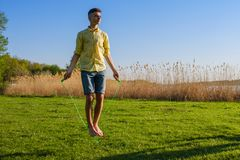 Young caucasian boy is doing workout with jumping rope on green grass lawn. Young caucasian boy is doing workout with jumping rope, on green grass lawn Royalty Free Stock Photo