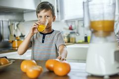 Young Caucasian boy drinking orange juice Stock Photography