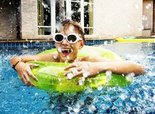 Young caucasian boy enjoying floating in the pool with tube Stock Photo