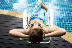 Young caucasian boy enjoying sunbathing by the pool Royalty Free Stock Photo