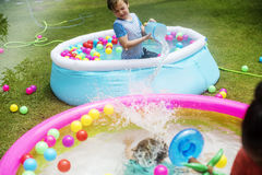 Young caucasian boy in inflatable pool enjoying water Royalty Free Stock Image