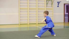 Young caucasian boy in national Chinese dress is practicing Kung Fu wushu tai chi form Nanquan southern fist exercises. Boy practises martial arts fighting stock footage