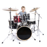 Young caucasian boy plays drums in studio against white backgrou Royalty Free Stock Photography