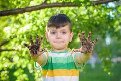 A young Caucasian boy showing off his dirty hands after playing. In dirt and sand outdoors sunny spring or summer evening on blossom trees background. happy Stock Photo