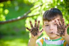 A young Caucasian boy showing off his dirty hands after playing. In dirt and sand outdoors sunny spring or summer evening on blossom trees background. happy Stock Photography
