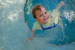 Young boy smiling as he plays in a pool. Young, Caucasian boy is smiling at the camera, wearing a face mask around his neck, as he plays and swims in a pool Royalty Free Stock Photo