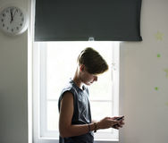Young caucasian boy using mobile phone in bedroom Stock Image