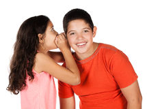 Young caucasian boy. Wearing a blue t-shirt and a cute caucasian girl wearing a pink top. They are whispering to each other Stock Photography