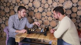 Young caucasian boys playing a game of chess together at home. Woodem frame background. stock video
