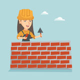 Young caucasian bricklayer building a brick wall. Caucasian bicklayer working with spatula at the construction site. Young female bricklayer in uniform and hard Stock Photography