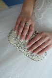 Young Caucasian bride with elegant manicure holding a beads and rhinestone embellished clutch Stock Photos