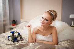 Young Caucasian bride laying on bed at home with bouquet closeup Stock Photos