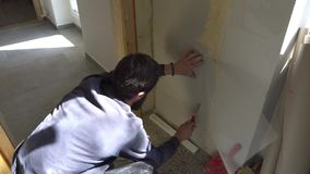 Worker spackle compound. Young caucasian brown haired beard man in dark purple pullover and track pants is measuring fixing and cutting with a stanley knife the stock footage