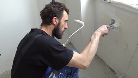 Wall paint worker. Young caucasian brown haired man with beard and black t-shirt blue dungarees working trousers is crouching down painting with paint brush and stock video footage